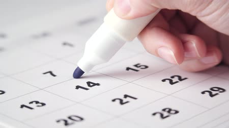 planejador : Signing a day on a calendar with blue pen or marker. Putting date in circle. Valentines day.