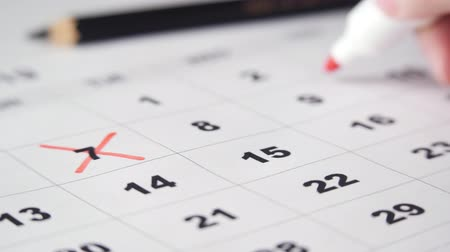 Signing a day on a calendar with red pen or marker. Crossing dates