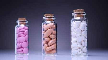 Colorful pills in bottles. Focus is sliding from background to foreground. 4k. Wideo