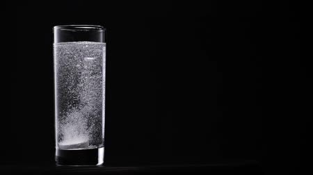 Dissolving effervescent tablets. White tablet in transparent glass on black background. Slowmotion.