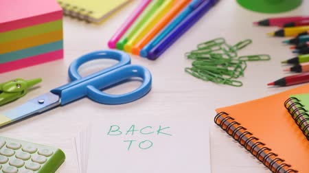 slider shot : Stop motion shot of a school desk with different colorful supplies. Words Back to school are showing up. 4k. Stock Footage