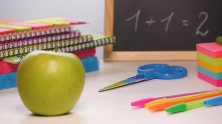 Shot of a school desk with different colorful supplies, apple and chalkboard. Back to school concept. Sliding focus. 4k. Wideo