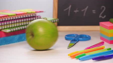 аксессуары : Shot of a school desk with different colorful supplies, and chalkboard. Green apple rolling in. Back to school concept. Sliding focus. 4k.