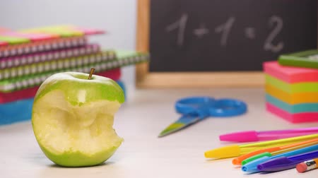 Stop motion shot of a school desk with different colorful supplies. Someone biting an apple. Back to school concept. 4k.