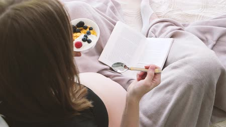 Pregnant woman is sitting on the bed and eating some berries while reading a book. 4k.