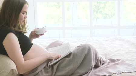 Pregnant woman is sitting on the bed and eating some berries and stroke her naked belly while reading a book. 4k.