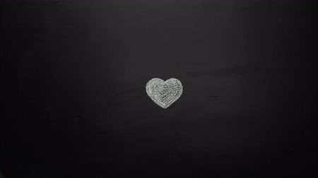 Heart beating stop motion. Heart drawn with chalk on black board getting bigeer and beating in the end. Wideo