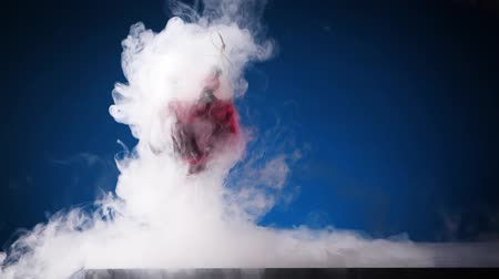 Smoking cocktail. Glass with red drink with berries. Pouring nitrogen from the top. Clouds of smoke spreading in slow motion.