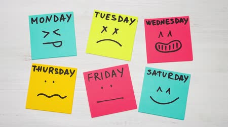 sticky notes with smiles and days of week. Different emotions. Stop motion.