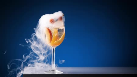 Smoking cocktail. Glass with yellow drink with berries and fruits. Clouds of smoke spreading in slow motion.