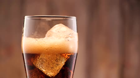 kola : Cola pouring in tall glass thish ice cubes ib slow motion. A lot of bubbles and sparkling.
