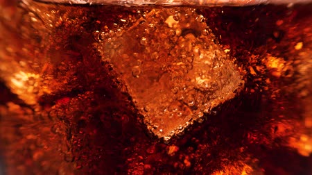 kola : Macro shot of glass with cola and ice cubes. A lot of bubbles going up. 4k. Stok Video