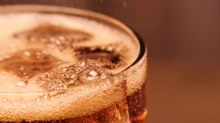 kola : Macro shot of glass with cola and ice cubes. Cola pouring in the glass. A lot of bubbles going up. 4k. Stok Video