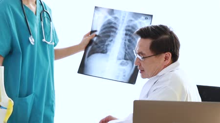 Medical professionals holding x-ray and conversation about patient.