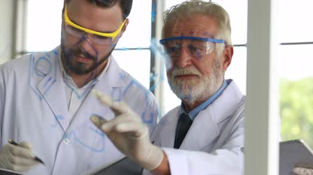 Medical researchers and scientist holding tablet to working in laboratory. Стоковые видеозаписи
