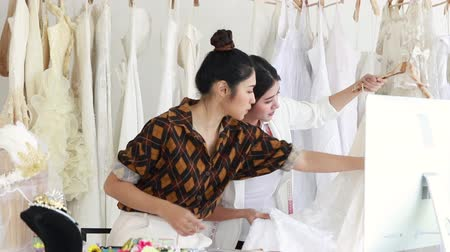 Young woman choosing dress in a shop with tailor assistant.