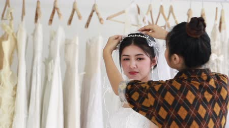 Young woman trying on wedding dress in a shop with tailor assistant.