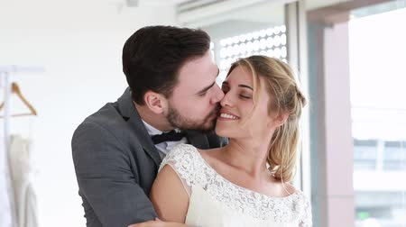 Bride and groom couple of Caucasian kiss and hug in wedding studio.