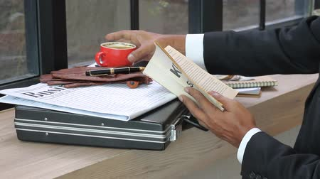 Business manager reading book and drinking coffee.