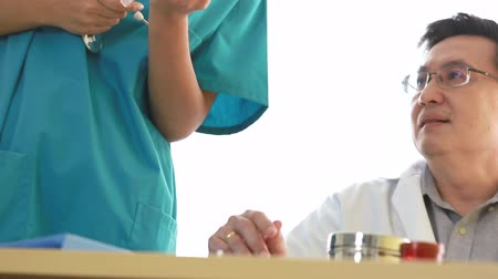 Doctor teaching medical student to use syringe.