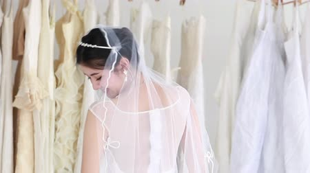 Young woman smiling and trying on wedding dress in a shop.