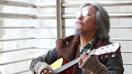 donate : Senior homeless artist playing guitar to make money on street.