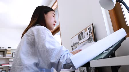 rolled : Young woman architect working from home, sketching a housing project. Stock Footage