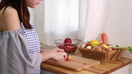 Young woman is cooking on kitchen. Having fun while slicing vegetables.