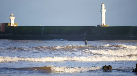 groyne : Surfers, strong waves and lighthouse in the North Sea Beach, Aberdeen, Scotland Stock Footage