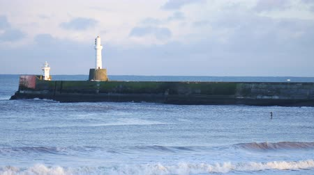groyne : Strong waves and lighthouse in the North Sea Beach, Aberdeen, Scotland
