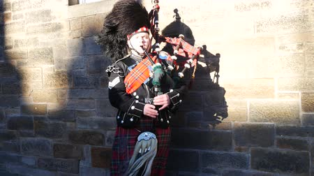 felvidéki : EDINBURGH, SCOTLAND  29 DECEMBER 2015: Traditional Scottish bagpiper in full dress code at Edinburgh Castle, Scotland. This is a traditional music of Scotland. Stock mozgókép