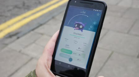 incorporated : ABERDEEN, UNITED KINGDOM - JULY 22, 2016: People playing Pokemon GO the hit augmented reality smart phone app while trying to find Pokemon on July 22, 2016 in Aberdeen, United Kingdom.