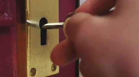 Дверная ручка : Hand of young man locks a door with a key