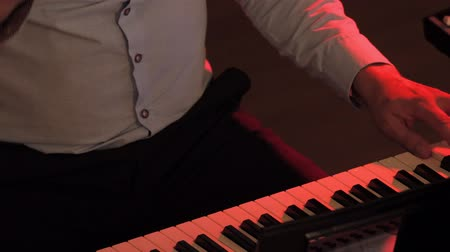 ピアノ : Playing electric piano under colorful stage lighting