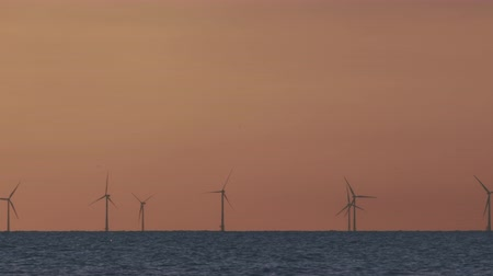 szélmalom : Wind turbines in the sea under sunset