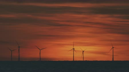 генератор : Wind turbines in the sea under sunset