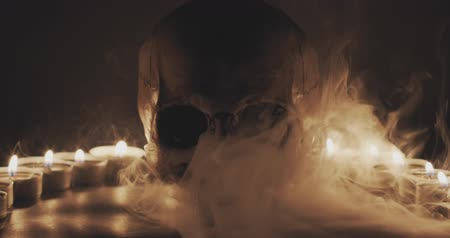 grim : Skull with smoke and candles in slow motion