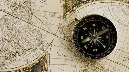 западный : Disorientated spinning compass against map background closeup footage Стоковые видеозаписи