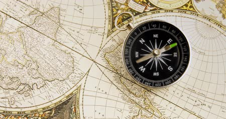к юго западу : Disorientated spinning compass against map background closeup footage Стоковые видеозаписи