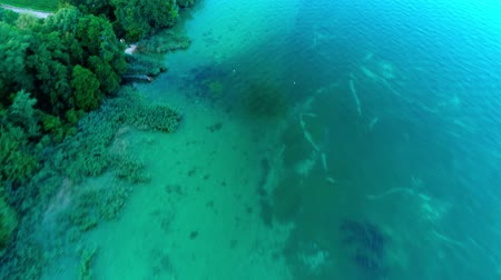montanhas rochosas : Magnificent 4k top drone aerial view on calm blue emerald water in wild nature forest green trees by ocean shore beach
