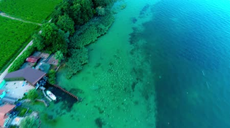 montanhas rochosas : Beautiful 4k top drone aerial view on calm blue emerald water in wild nature green tree field farm by ocean shore beach
