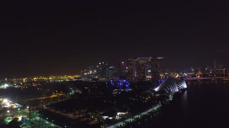 照らさ : Fascinating 4k aerial drone view on big city Singapore by ocean metropolis downtown in bright night light illumination