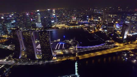 照らさ : Stunning 4k aerial drone view on big city Singapore by ocean metropolis downtown in bright night light illumination