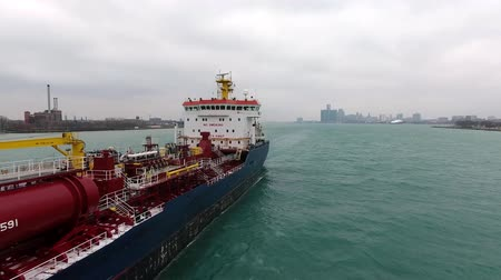 vessels : Huge container cargo freight tanker ship sailing slowly in calm ocean bay in big city harbour in aerial drone seascape