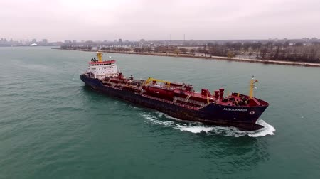 global business : Drone aerial seascape view on big cargo container freight tanker ship sailing slowly in ocean water in big city harbour Stock Footage