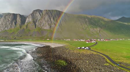 vízfelület : Amazing rainbow over blue ocean waves crashing on stone beach in rural mountain hill village 4k aerial drone landscape Stock mozgókép