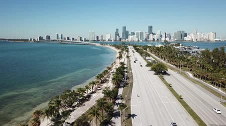 tropikal iklim : Incredible aerial 4k drone panorama flight over huge highway road in big city Miami East Coast ocean coastline seascape Stok Video