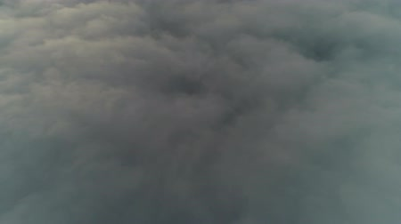 Flying over white fluffy rain clouds in evening sky in abstract beautiful 4k aerial drone view