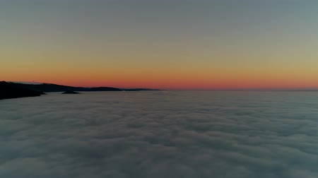 dolu : Picturesque 4k aerial drone flight over sunset sky full of white fluffy clouds in warm orange evening sun light