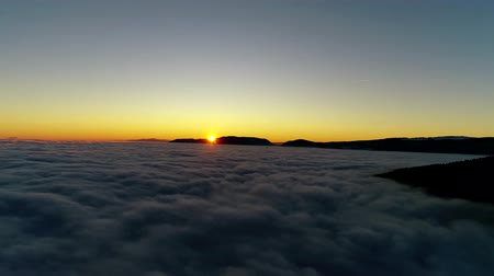 dolu : Gorgeous 4k aerial drone flight over sunset sky full of white fluffy clouds in warm orange evening sun light Stok Video